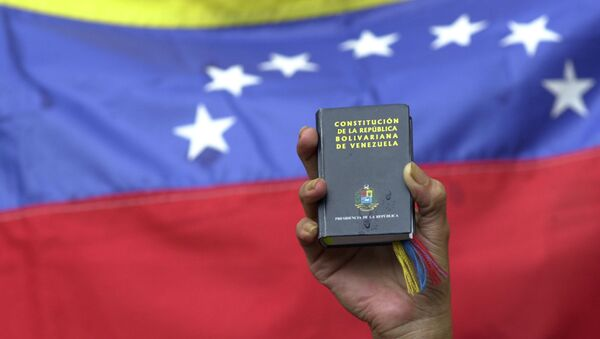 A demonstrator holds up a miniature copy of Venezuela's constitution in front of the nation's flag at a government rally in Caracas, Venezuela, Tuesday, April 13, 2004. - Sputnik International