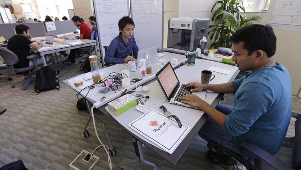In this Thursday, June 30, 2016 photo, Babson College graduate school alumnus Abhinav Sureka, of Mumbai, India, right, types in his work space at the college in Wellesley, Mass. Some U.S. colleges are starting programs to help their alumni get visas through what critics say is a legal loophole - Sputnik International