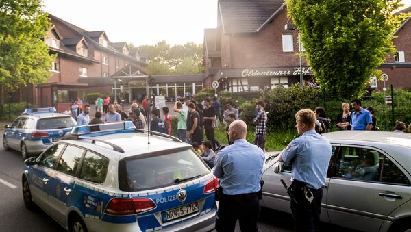 In this May 21, 2016 picture police and refugees stand near a refugee shelter in Bielefeld, Germany - Sputnik International