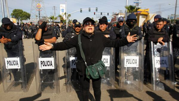 A demonstrator gestures in front of policemen as a group of them blocked the entrance of a Pemex gas storage station during a protest against the rising prices of gasoline enforced by the Mexican government, in Rosarito, Mexico, January 7, 2017. - Sputnik International