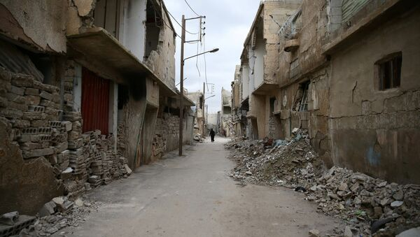 A woman walks past damaged buildings in the rebel held besieged city of Douma, in the eastern Damascus suburb of Ghouta, Syria - Sputnik International