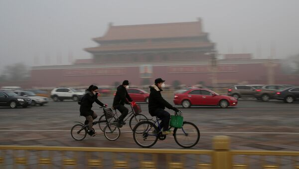 People wearing masks cycle past Tiananmen Gate during the smog after a red alert was issued for heavy air pollution in Beijing, China, December 20, 2016. - Sputnik International