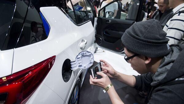Посетитель фотографирует электрический разъем китайского автомобиля GE3 на автосалоне в Детройте - Sputnik International