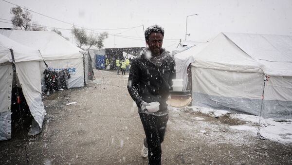 A migrant walks after receiving food during snowfall at the Moria hotspot on the Greek island of Lesbos, on January 9, 2017. - Sputnik International