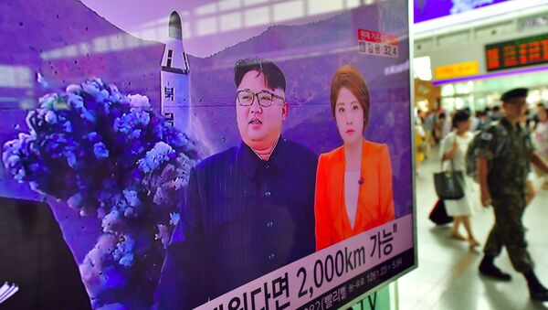 A South Korean soldier (R) walks past a television screen reporting news of North Korea's latest submarine-launched ballistic missile test at a railway station in Seoul on August 25, 2016 - Sputnik International