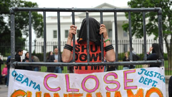 A hooded demonstrator is seen at a protest calling for the closure of the Guantanamo Bay detention facility in front of the White House on May 18, 2013 in Washington, DC. - Sputnik International