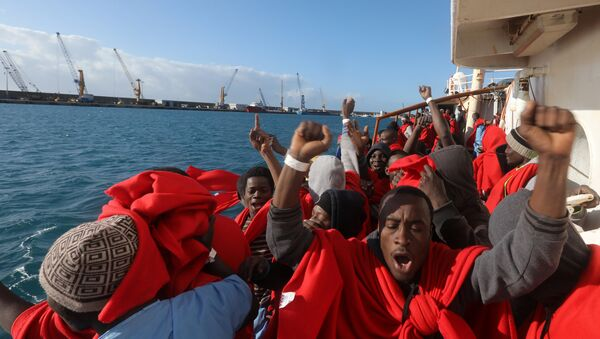Migrants celebrate on board the former fishing trawler Golfo Azzurro as they arrive at the port of Pozzallo in Sicily, two days after they were rescued by the Spanish NGO Proactiva Open Arms after the raft they were on drifted out of control in the central Mediterranean Sea, January 4, 2017 - Sputnik International