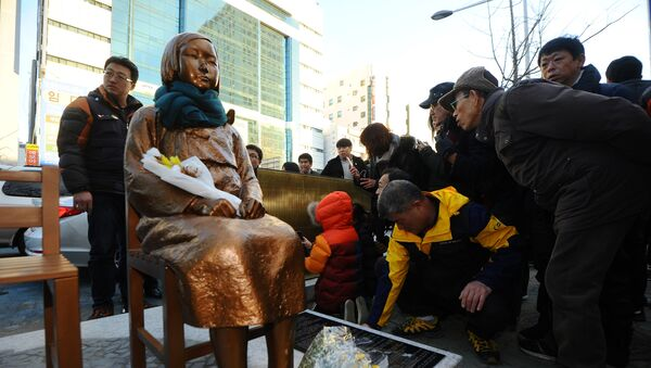 A flower is laid on a statue of a girl that represents the sexual victims by the Japanese military during a rally in front of Japanese Consulate in Busan, South Korea, December 30, 2016. Picture taken December 30, 2016 - Sputnik International