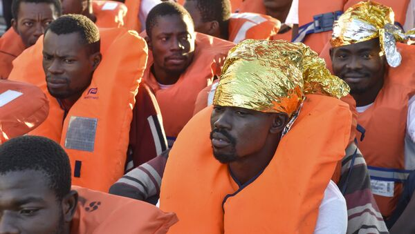 Migrants and refugees wait to be trasferred from the Topaz Responder ship run by Maltese NGO Moas and the Italian Red Cross to the Vos Hestia ship run by NGO Save the Children, on November 4, 2016, a day after a rescue operation off the Libyan coast in the Mediterranean Sea. - Sputnik International