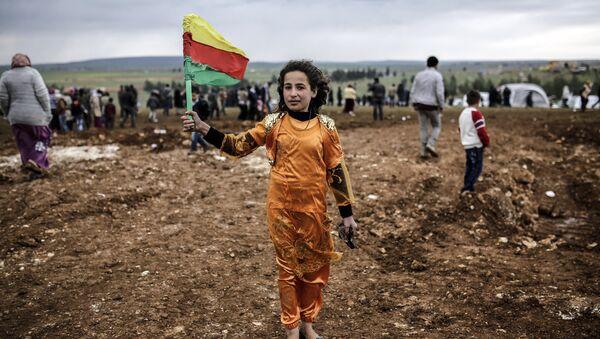 A Syrian Kurdish young woman holds the flag of the Syrian Kurdish Democratic Union Party (PYD) (File) - Sputnik International