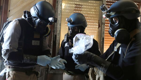 A U.N. chemical weapons expert, wearing a gas mask, holds a plastic bag containing samples from one of the sites of an alleged chemical weapons attack in the Ain Tarma neighbourhood of Damascus, Syria. (File) - Sputnik International