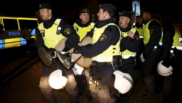 A migrant is carried out by police officers from an illegal camp set up in Malmoe - Sputnik International