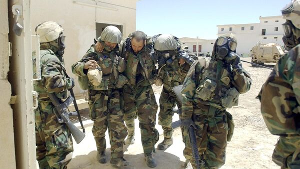 A US Army soldier from 2-8 Infantry, 2nd Brigade, 4th Infantry Division wearing his full chemical protection suit and suffering from heat exhaustion is helped by other soldiers after they sucured an industrial complex which they thought was a possible site for weapons of mass destruction in the central Iraqi town of Baquba 01 May 2003. - Sputnik International