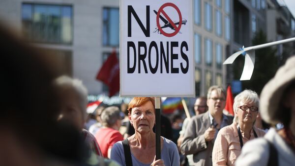 A woman holds a poster against drones during a demonstration against the upcoming visit of United States President Barack Obama in Berlin, Monday, June 17, 2013 - Sputnik International