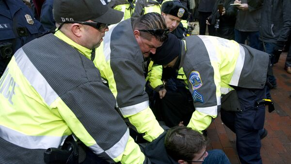 Police try to remove a demonstrator from attempting to block people entering a security checkpoint, Friday, Jan. 20, 2017, ahead of President-elect Donald Trump's inauguration in Washington - Sputnik International