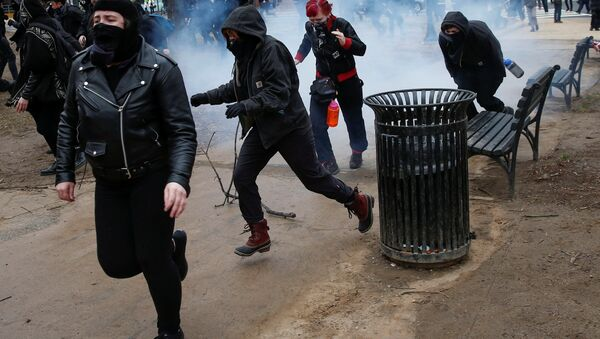 Activists race after being hit by a stun grenade while protesting against U.S. President-elect Donald Trump on the sidelines of the inauguration in Washington, U.S., January 20, 2017. - Sputnik International