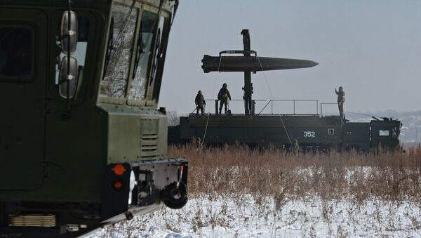 Russian soldiers watch a transporter-loader place an Iskander-M shorter-range missile onto a self-propelled launcher - Sputnik International