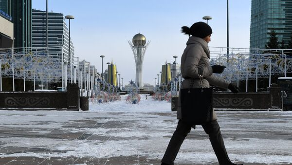 A picture taken on January 22, 2017 shows a woman walking in downtown Astana, with the Baiterek monument seen in the background - Sputnik International