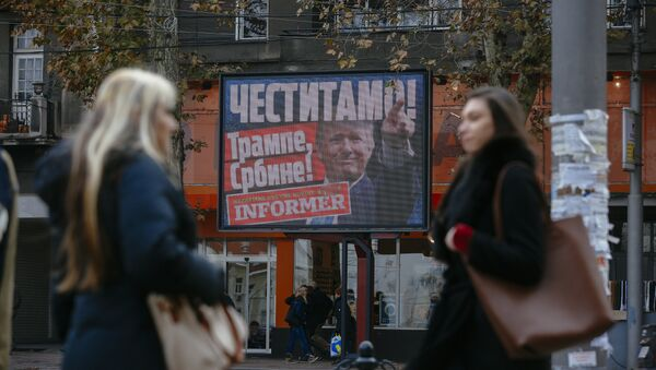 Pedestrians walk by a billboard picturing US President-elect Donald Trump with an inscrpition that translates as Congratulations! Trump, Serb! published by Serbian daily newspaper in Belgrade on November 10, 2016 - Sputnik International