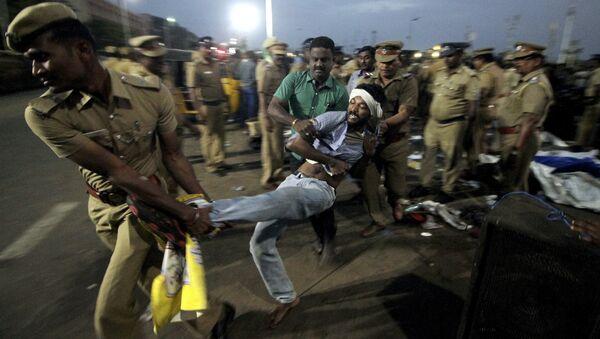 A protestor supporting Jallikattu, a traditional bull-taming ritual tries to resist as police remove them from the Marina beach on the Bay of Bengal coast in Chennai, India, Monday, Jan.23, 2017. - Sputnik International