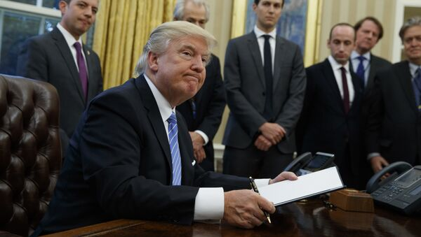 President Donald Trump looks up after signing the final of three executive orders, Monday, Jan. 23, 2017, in the Oval Office of the White House in Washington. (AP Photo/Evan Vucci) - Sputnik International