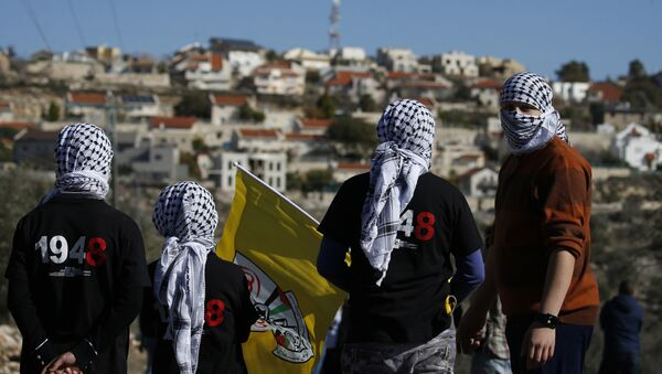Palestinian protestors stand facing the Israeli settlement of Qadumim (Kedumim) during clashes with Israeli security forces following a demonstration against the expropriation of Palestinian land by Israel in the village of Kfar Qaddum, near Nablus, in the occupied West Bank on December 30, 2016 - Sputnik International