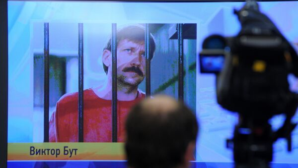 A journalist stands near a screen displaying convicted Russian arms smuggler Viktor Bout in Moscow, on April 12, 2012, during a teleconference with Bout from his US prison - Sputnik International