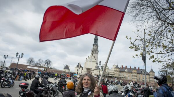 A woman waves a Polish flag in front of the Jasna Gora monastery during the annual Polish motorcyclists pilgrimage to the country's greatest place of pilgrimage hosting the Black Madonna of Czestochowa in Czestochowa, Poland, on April 19, 2015 - Sputnik International