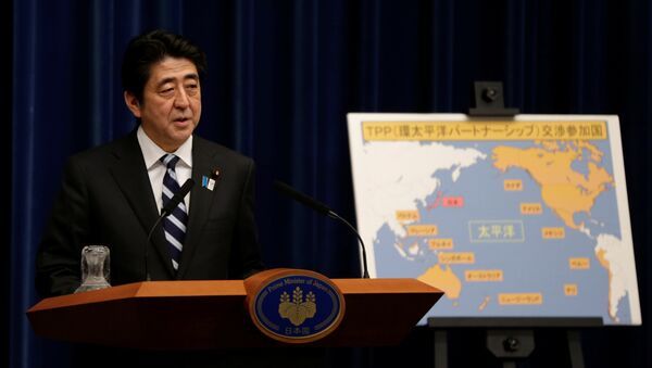 Japan's Prime Minister Shinzo Abe speaks next to a map showing participating countries in rule-making negotiations for the Trans-Pacific Partnership (TPP) during a news conference at his official residence in Tokyo (File) - Sputnik International