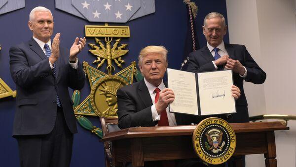 US President Donald Trump shows his signature on executive orders alongside US Defense Secretary James Mattis and US Vice President Mike Pence on January 27, 2017, at the Pentagon in Washington, DC - Sputnik International