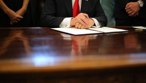 US President Donald Trump prepares to sign an executive order cutting regulations, accompanied by small business leaders at the Oval Office of the White House in Washington US, January 30, 2017. - Sputnik International