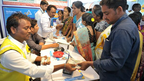 An Indian visitor (R) receives cash from a bank employee after withdrawing money from his bank account with his Aadhaar or Unique Identification (UID) card during a Digi Dhan Mela, held to promote digital payment, in Hyderabad on January 18, 2017 - Sputnik International