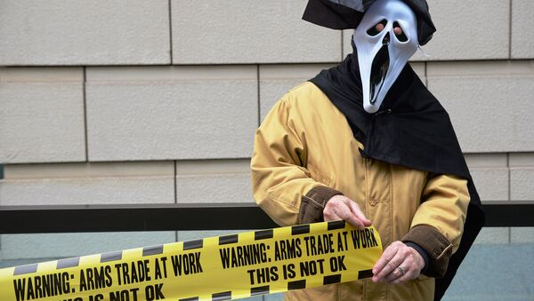 A demonstrator from 'Stop G8' is pictured outside the offices of BAE Systems in London on June 12, 2013, during a protest against the G8 Summit. - Sputnik International