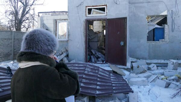 A woman by a house damaged by the shelling of the Ukrainian army in Donbass - Sputnik International