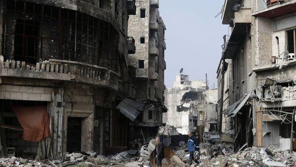 Syrians walk through the destruction in the old city of Aleppo, Syria - Sputnik International