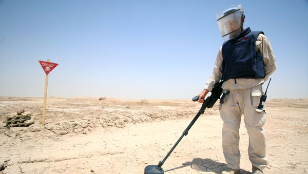 An Iraqi man wearing protective gear searches for landmines in the Shalamja border crossin, west of Basra, on the border between Iraq and Iran, on June 10, 2015 - Sputnik International