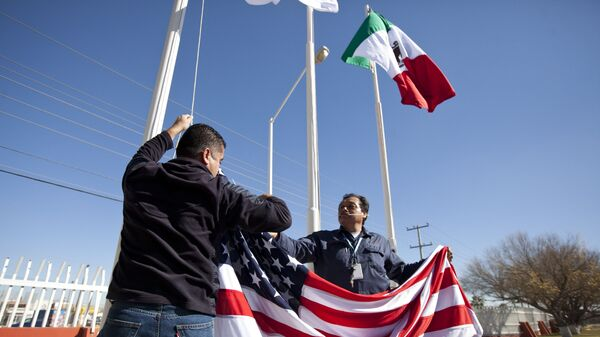 In this Friday, Dec. 27, 2013 photo, workers at one of maquiladoras of the TECMA group prepare to raise the U.S. flag along with the Mexican and TECMA flags in Ciudad Juarez, Mexico - Sputnik International