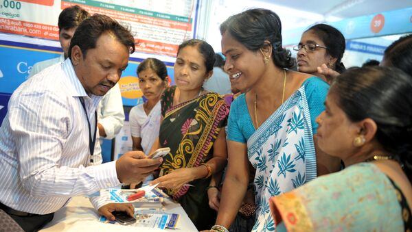 An Indian bank employee (L) explains to visitors about account transactions from a mobile phone with a Aadhaar or Unique Identification (UID) card during a Digi Dhan Mela, held to promote digital payment, in Hyderabad on January 18, 2017 - Sputnik International
