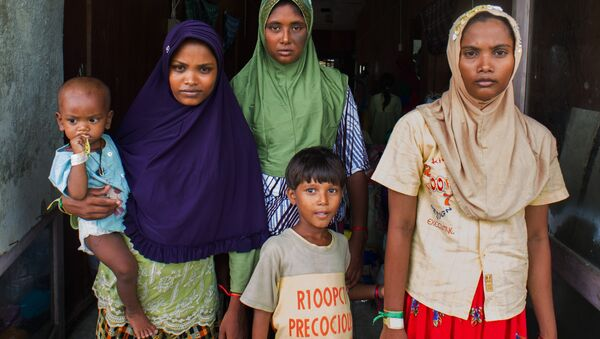 In this photograph taken on May 28, 2015, Rohingya migrant women from Myanmar (L-R) Rubuza Hatu, 21, Rehana Begom, 24 and Rozama Hatu, 23, stand at a confinement camp at Bayeun district in Indonesia's Aceh province after Indonesian fishermen rescued about 400 Rohingya migrants from Myanmar and Bangladesh from a boat on May 20, 2015 off the eastern coast of Aceh. - Sputnik International