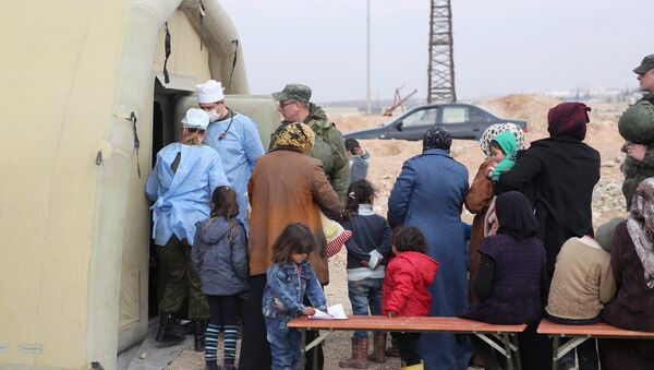 Syria. Treating people at the Jibrin temporary refugee accommodation center in Aleppo. This re-cropped photo courtesy of the Russian Center for Reconciliation of the Warring Parties in Syria - Sputnik International