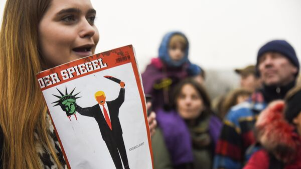 A young woman holds the last edition of Der Spiegel magazine with a cover designed by Edel Rodriguez, as she protests against the travel ban imposed by US President Donald Trump, on February 4, 2017, in Berlin - Sputnik International