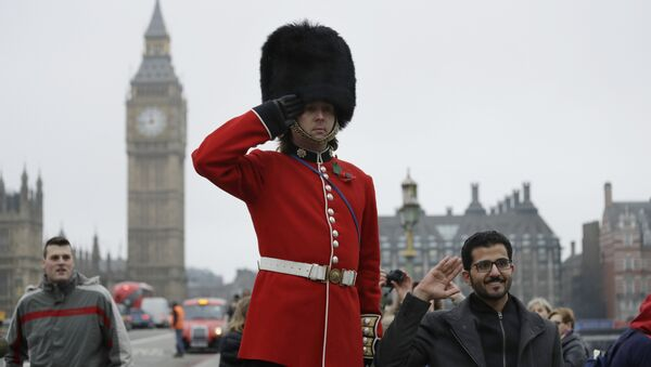 A man on stilts dressed in a ceremonial guardsman costume poses for photographs for tourists as he hands out flyers and collects money for charity on the southern end of Westminster Bridge backdropped by the Houses of Parliament in London, Wednesday, February 8, 2017. - Sputnik International