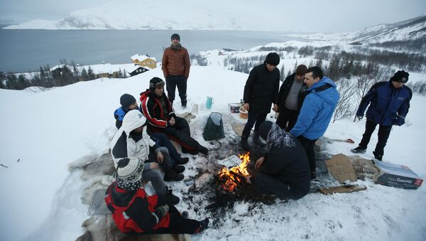 Asylum seekers gather round a fire as they cook a meal overlooking the temporary Altnes camp refugee camp on the island of Seiland, northern Norway - Sputnik International