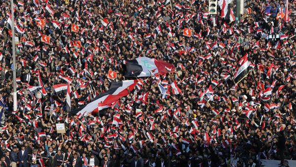 Followers of Iraq's influential Shiite cleric Muqtada al-Sadr chant slogans as they wave national flags during a demonstration against corruption in Baghdad, Iraq - Sputnik International