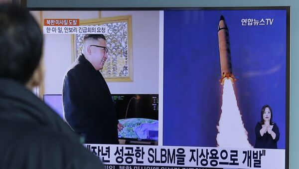 A man watches a TV news program showing photos published in North Korea's Rodong Sinmun newspaper of North Korea's Pukguksong-2 missile launch and North Korean leader Kim Jong Un at Seoul Railway Station in Seoul, South Korea, Monday, Feb. 13, 2017 - Sputnik International