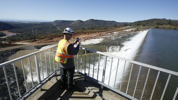 In this Saturday, Feb. 11, 2017, photo, Jason Newton, of the Department of Water Resources, takes a picture of water going over the emergency spillway at Oroville Dam in Oroville, Calif - Sputnik International