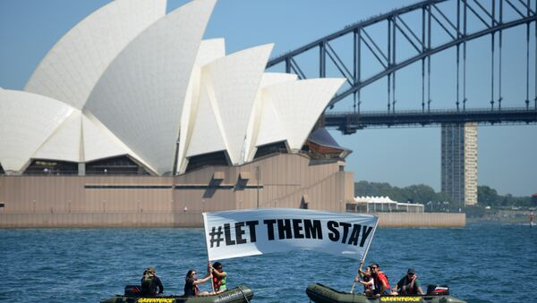 Members of the environmental group Greenpeace hold up a sign that reads #LET THEM STAY in front of the Opera House in Sydney on February 14, 2016. - Sputnik International