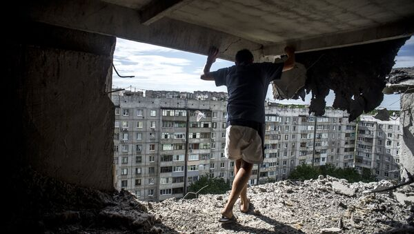 Man inspects damaged residential building in the Mirny district of Lugansk, hit by artillery fire. File photo - Sputnik International