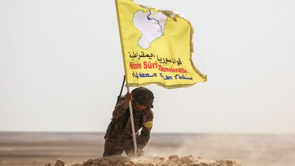 A member of the Syrian Democratic Forces (SDF), made up of US-backed Kurdish and Arab fighters, raises a flag of the SDF near the village of Bir Fawaz, 20 km north of Raqqa, during their offensive towards the Islamic State (IS) group's Syrian stronghold as part of the third phase retake the city and its surroundings, on February 8, 2017 - Sputnik International