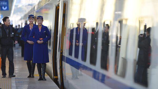 Train conductors stand outside the cabin of a bullet train - Sputnik International